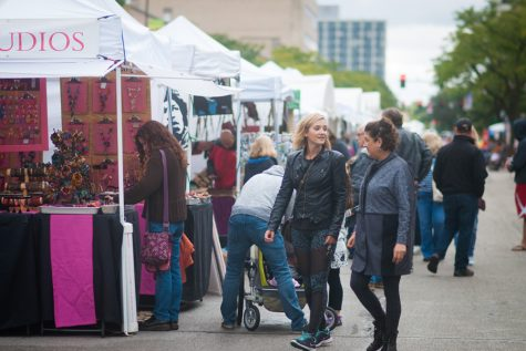 Two women chat as they walk through the Evanston Art and Big Fork Festival. Vendors were selling anything from paintings and photography to home accessories and hand-made jewelry.