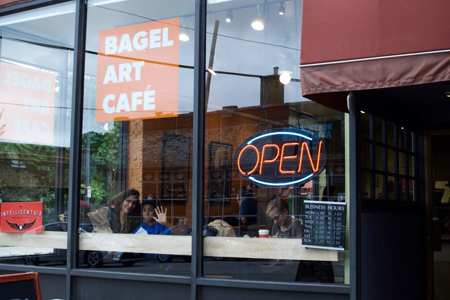 A+boy+looks+out+the+window+of+Bagel+Art+Cafe%2C+615+Dempster+St.+The+shop+reopened+on+Sundays+this+weekend.+