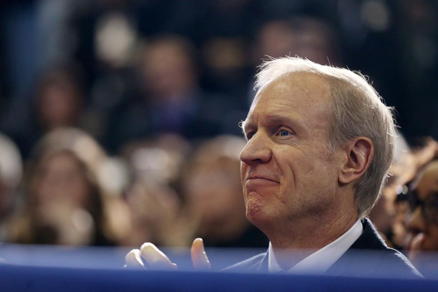 Gov. Bruce Rauner listens to President Barack Obama speak in Chicago. Rauner is trying to get the Illinois House of Representatives to pass a bill that would provide state ID's to convicts when they are released from prison.