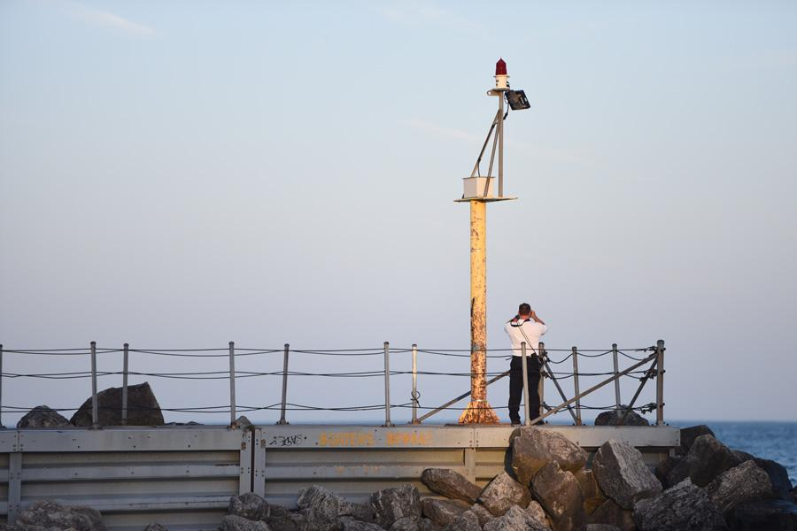 An official looks off a pier into Lake Michigan during the efforts to rescue a windsurfer on Monday afternoon. The man was rescued after a search of roughly one hour.