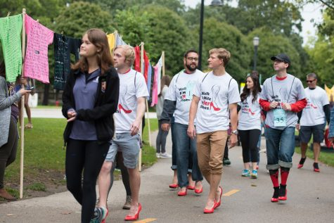 Participants in Walk a Mile in Her Shoes check out T-shirts made by the Clothesline Project. The project encourages victims of sexual assault to write their experiences on a T-shirt, which are then displayed for others to see.