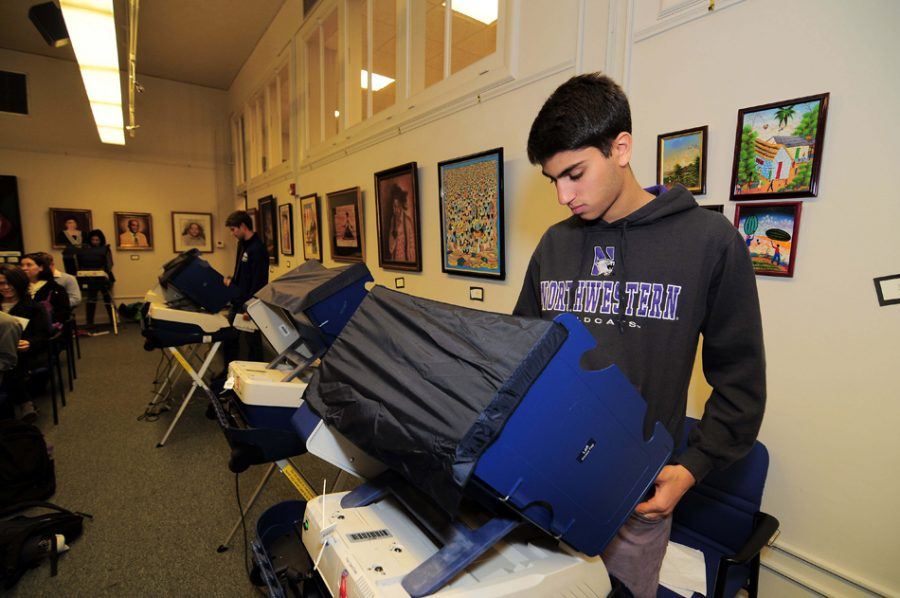 A Northwestern student casts his ballot at the Civic Center in 2014. Early voting in suburban Cook County starts next week.