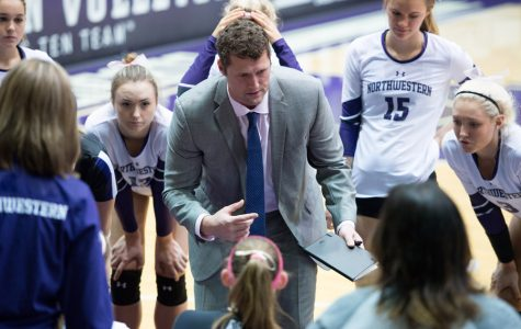 Coach Shane Davis talks to his team in a huddle. Although the Cats have struggled this year in Davis' rookie year, he remains confident in the future of NU volleyball.