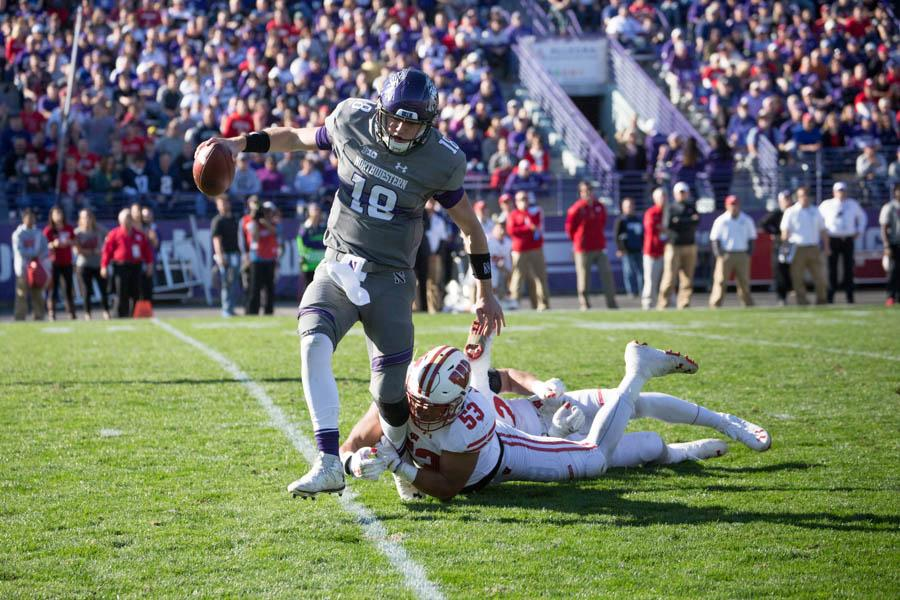 Clayton Thorson runs from defenders. The sophomore quarterback fumbled early in the fourth quarter, essentially sealing the win for Wisconsin on Saturday.