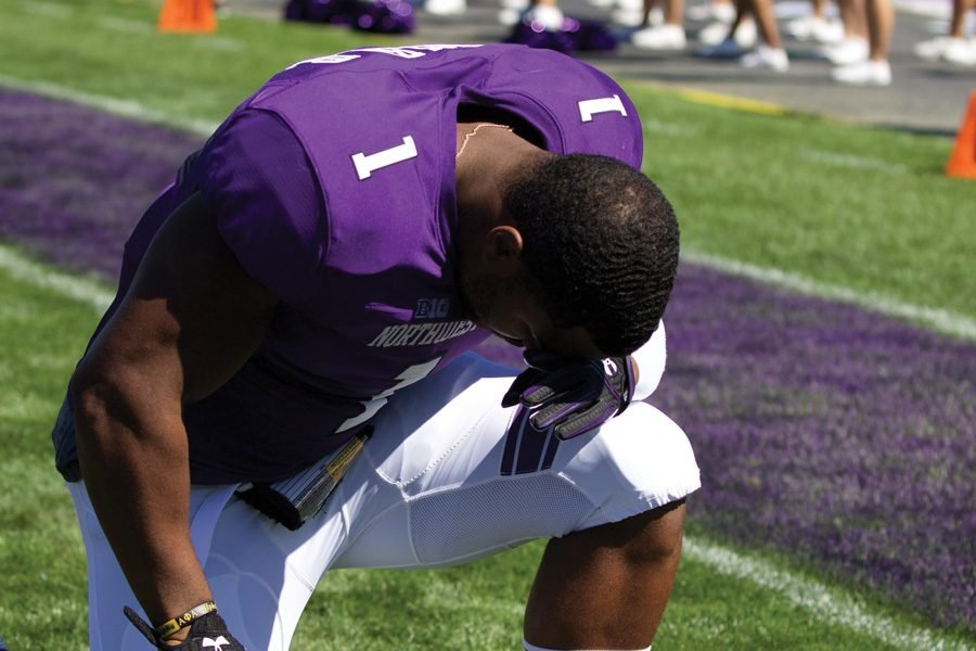 Anthony Walker kneels before a game. Walker announced on Friday through a tweet that he will enter the NFL Draft.