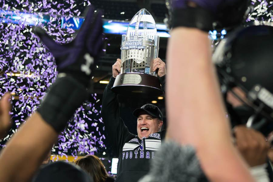 Coach Pat Fitzgerald raises the George Steinbrenner Trophy after Northwestern's Pinstripe Bowl victory. Fitzgerald is the first coach in program history to win two bowl games.
