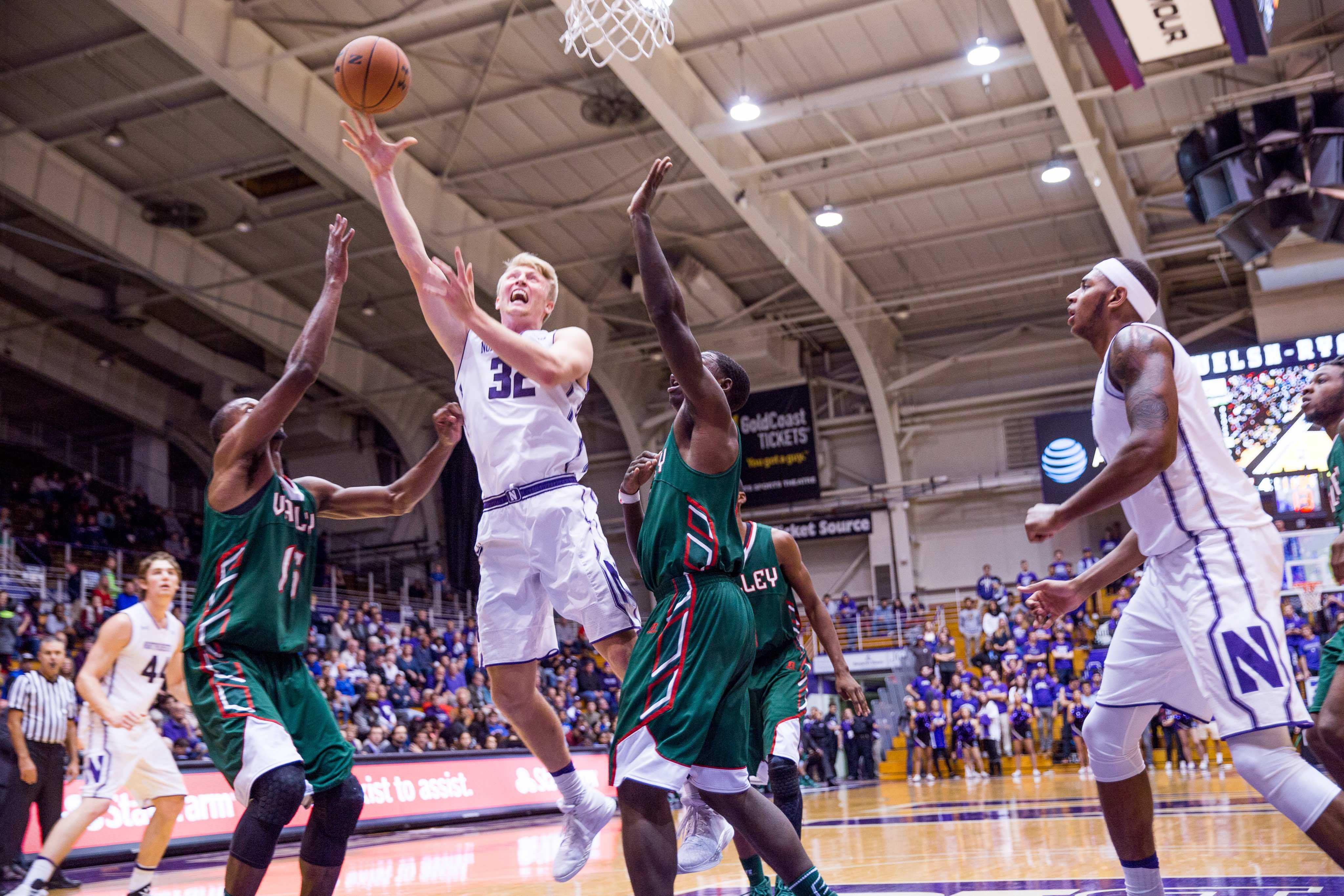 Nathan Taphorn attempts a layup between two defenders. The senior forward scored a career-best 18 points against New Orleans.