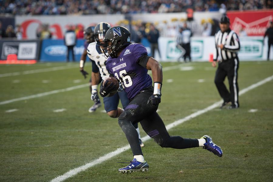 (Daily file photo by Colin Boyle) Godwin Igwebuike runs with the ball in the Pinstripe Bowl. The junior will return to Northwestern for a senior season.