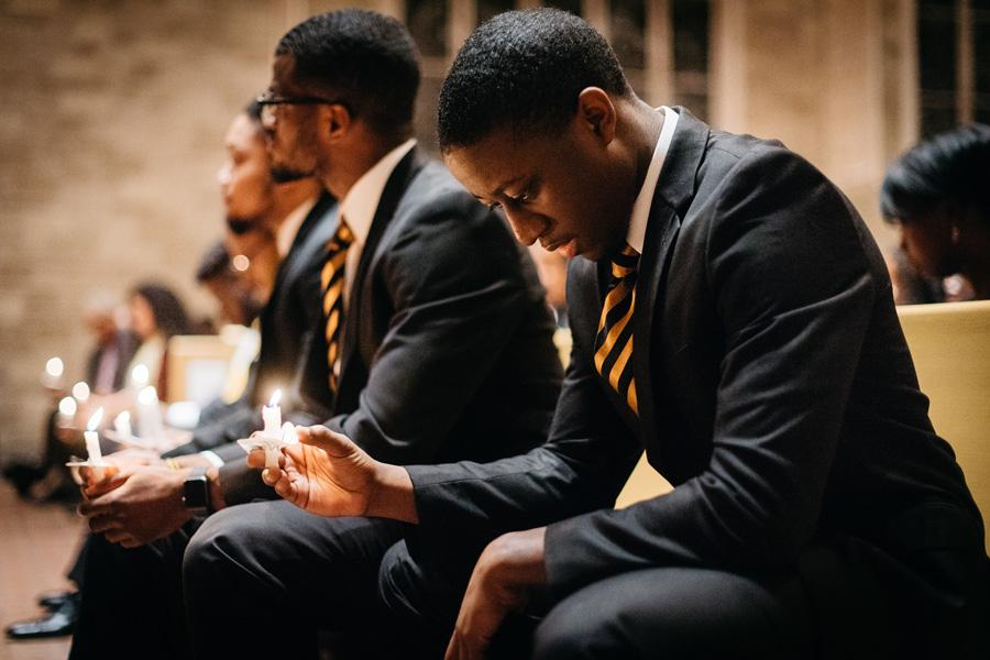Brothers of Alpha Phi Alpha sit in silence as they hold their candles to honor the legacy of Martin Luther King, Jr. The event was held as part of a two-week long series to reflect on King's lessons as a community.