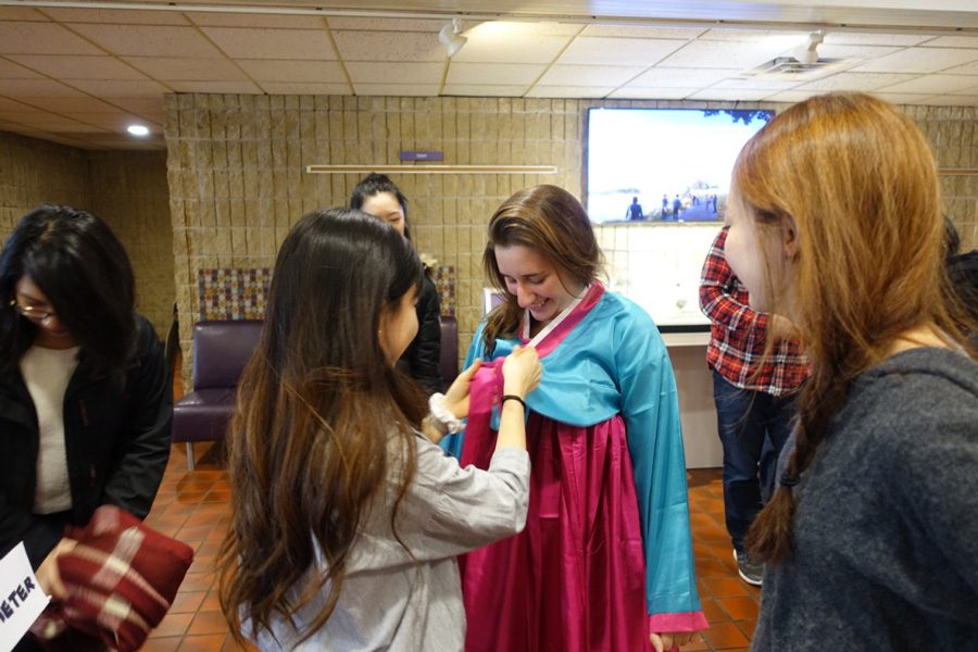 A+member+of+KASA+dresses+another+student+in+a+hanbok%2C+a+traditional+Korean+dress.+KASA+held+programming+Thursday+to+celebrate+the+Lunar+New+Year.