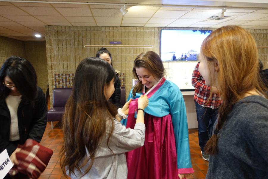 A member of KASA dresses another student in a hanbok, a traditional Korean dress. KASA held programming Thursday to celebrate the Lunar New Year.