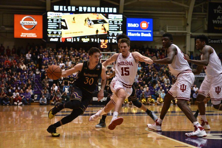 Bryant McIntosh drives past Indiana defenders. Northwestern's win over the Hoosiers helped push it into the AP Top 25.