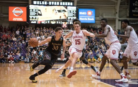 Bryant McIntosh drives past defenders. The junior guard will look to lead Northwestern back on the winning track against Illinois.