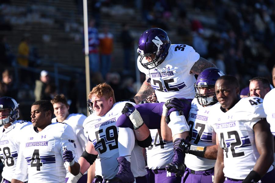 Northwestern players lift a teammate on their shoulders in 2016. The National Labor Relations Board's general counsel said in a memo that college football players at private universities can seek certain employee benefits.