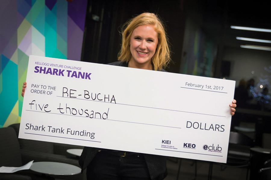 Kathryn Bernell holds a check after pitching her kombucha startup at the first Kellogg Venture Challenge Shark Tank. The startup features healthy and organic kombucha beverages.
