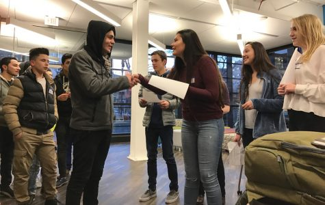 Two teenagers greet each other at Beacon Academy, 1574 Sherman Ave., Friday evening. Beacon students hosted about 30 Syrian refugees for dinner.