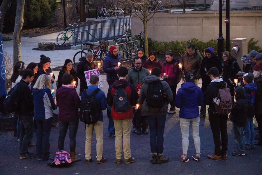 Students gather at the Rock for a vigil commemorating those affected by an executive order barring citizens of seven Muslim-majority countries from entering the United States. The event was hosted by Canterbury House and featured participants of diverse faiths.