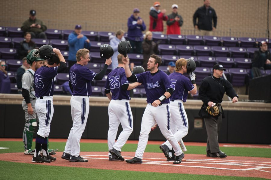 Several Wildcats celebrate at the plate. NU recorded a 2-0 win over Chicago State on Wednesday.