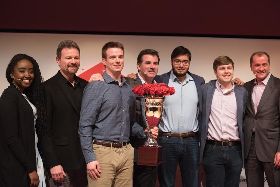 SwineTech founder Matthew Rooda stands with judges and other contestants at the Cupid's Cup Entrepreneurship Competition. SwineTech, which developed technology to prevent piglet deaths in pig farms, won the $75,000 grand prize.