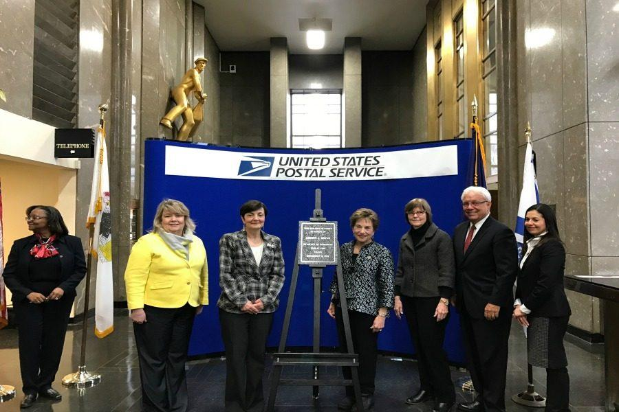 Postal officials, family members and local politicians stand in front of a plague dedicated to the late progressive icon, Abner Mikva. More than 70 people gathered Monday to honor Mikva, who once represented Evanston in Congress.