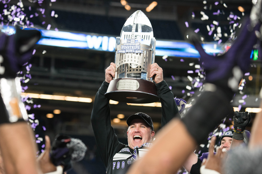 Pat Fitzgerald celebrates with the Pinstripe Bowl trophy. The football coach received a contract extension that will keep him in Evanston until 2026.