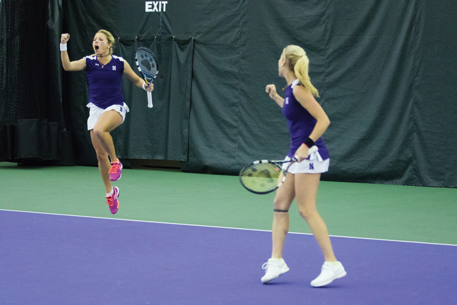 Alex Chatt (left) celebrates a point with her doubles partner, Maddie Lipp. The juniors and the Wildcats are seeking to extend their unbeaten start to Big Ten play.
