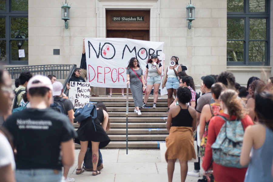 Students gather outside Harris Hall to protest the visit of an Immigration and Customs Enforcement representative Tuesday. The ICE representative had been invited to speak at a sociology class.