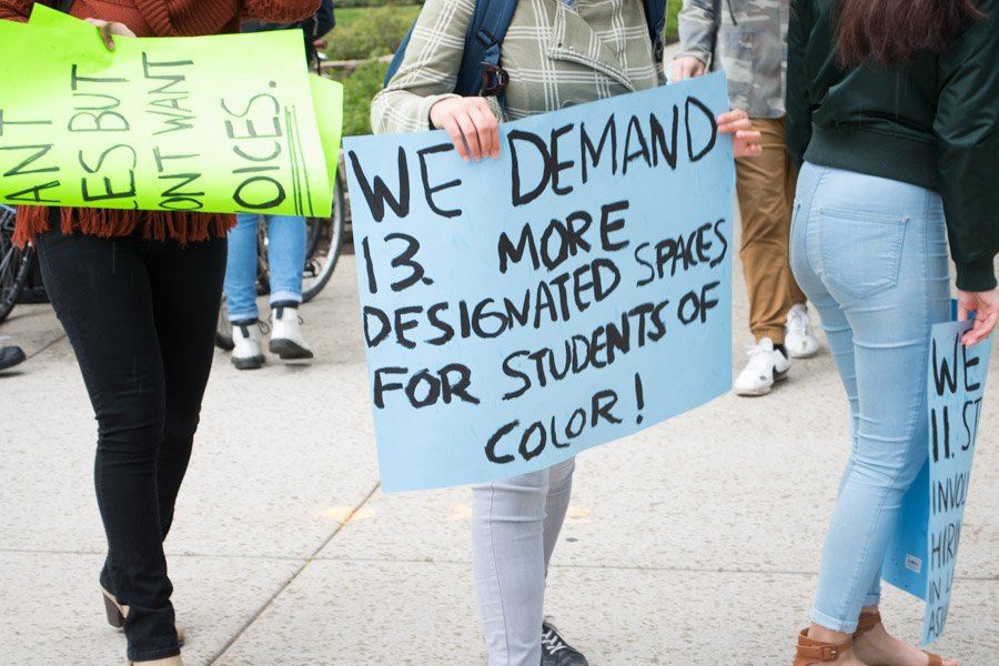 A student holds a poster during a silent protest held Friday outside Scott Hall. Following a May 16 protest against an ICE public relations representative, some student protesters are going through the University's conduct process.