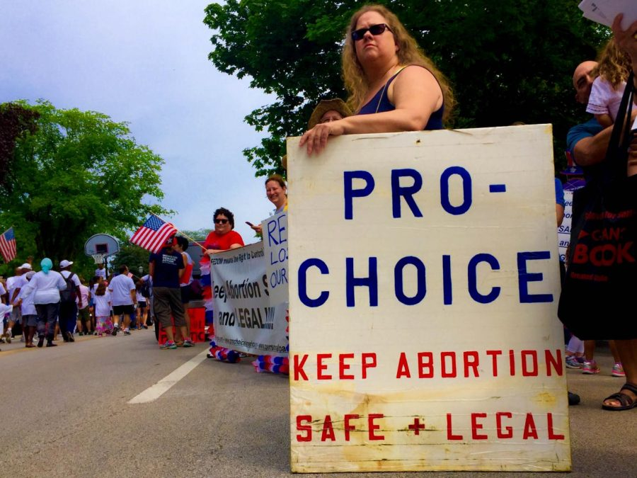 An+abortion+rights+activist+stands+on+the+sides+of+the+Evanston+parade+to+voice+her+opinions.+Some+attendees+used+the+parade+as+an+opportunity+to+advocate+for+social+and+political+issues.+