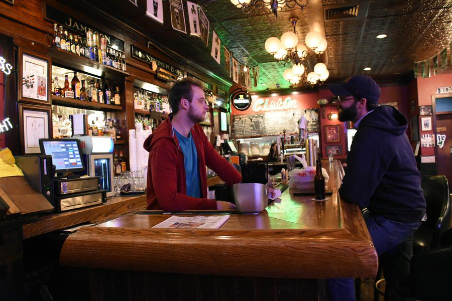 A customer is served at Tommy Nevin's Pub, located on Sherman Avenue. The popular bar for Northwestern students is for sale and will be demolished if a proposed 16-story apartment tower is approved by the City of Evanston.