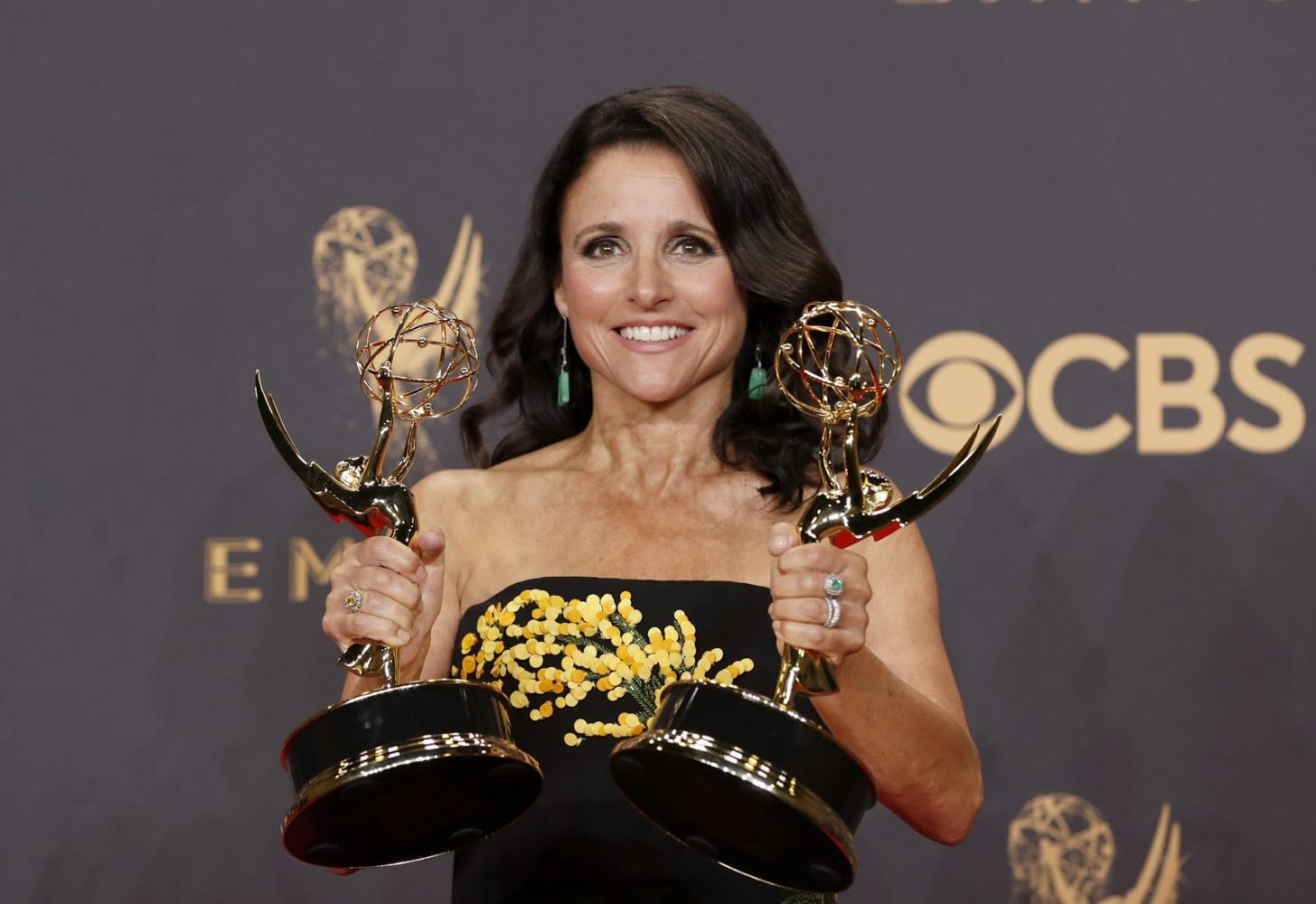 """Julia Louis-Dreyfus holds up two Emmys at the 69th Primetime Emmy Awards. Louis-Dreyfus (Communication '83) won her sixth consecutive Emmy for outstanding lead actress in a comedy series for her role on """"Veep."""" On Thursday, Louis-Dreyfus announced she had been diagnosed with breast cancer."""