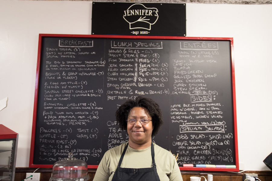 Jennifer Eason, owner of Jennifer's Edibles, poses in front of a store menu. The restaurant, 1623 Simpson St., received both a microloan and business services through LEND.