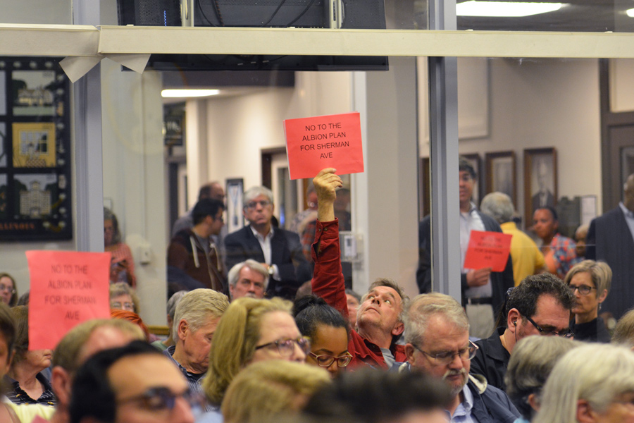A resident holds up a sign opposing Albion's proposed apartment tower. The development has caused controversy in Evanston.