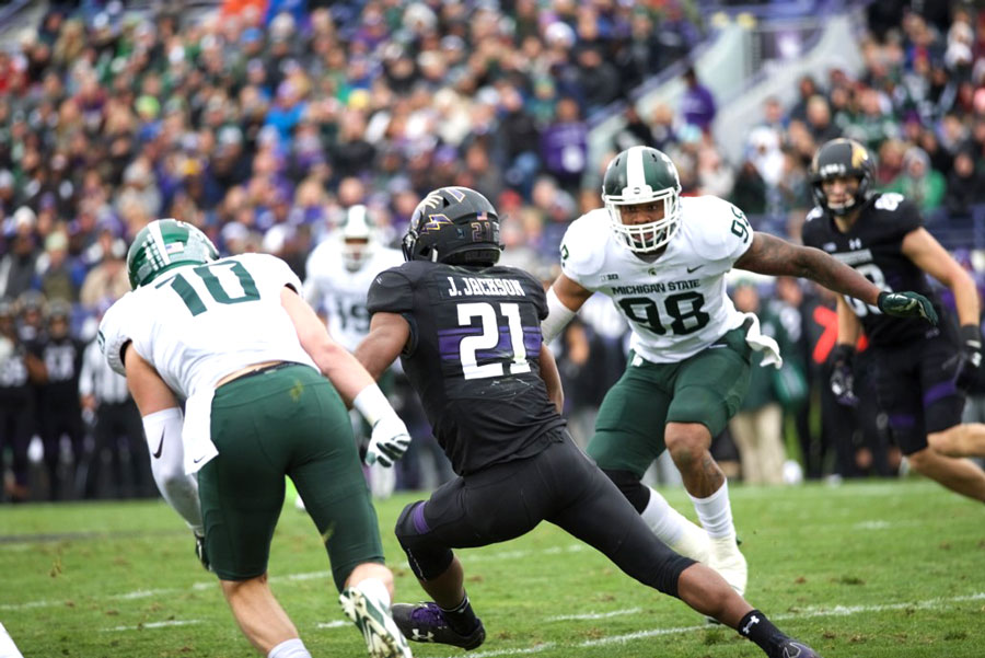Justin Jackson darts upfield. The senior running back contributed to Northwestern's win over Michigan State on Saturday in a variety of ways.