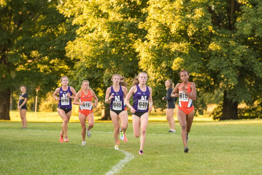 Three Northwestern runners round a turn. The Wildcats will compete at NCAA Pre-Nationals this weekend.