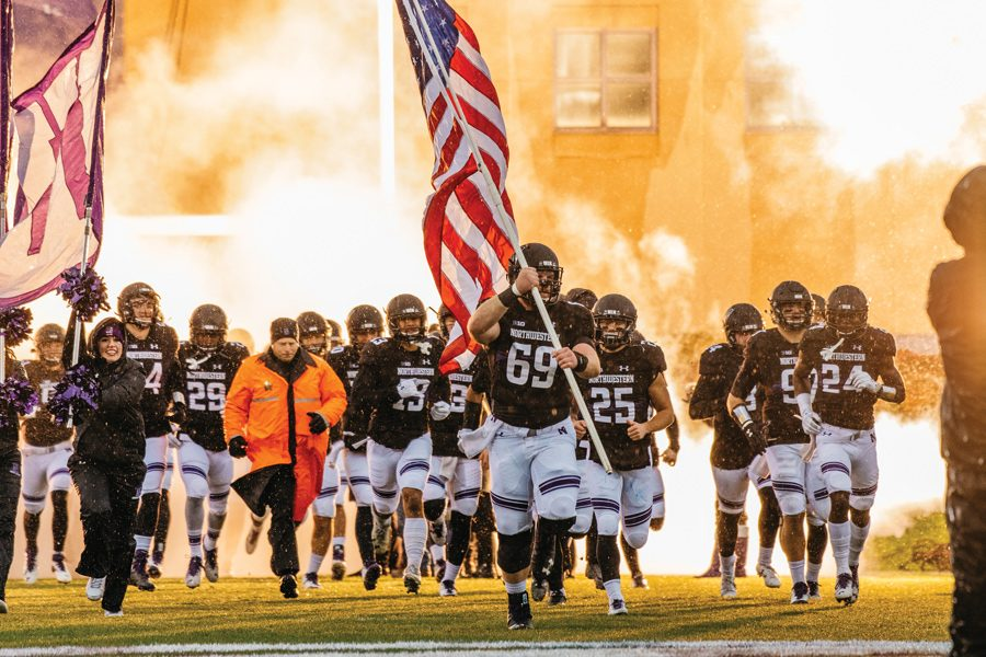 Brad North leads the Wildcats onto the field. The senior center and NU are looking to extend their winning streak at Illinois this weekend.