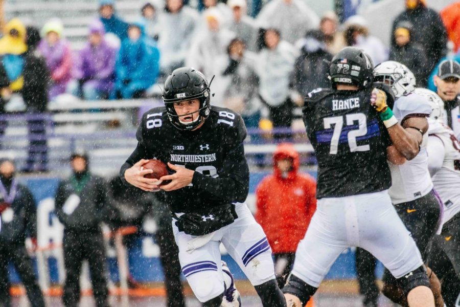 Clayton+Thorson+runs+through+the+sleet.+The+junior+quarterback+passed+13+times+at+soggy+Ryan+Field+on+Saturday.
