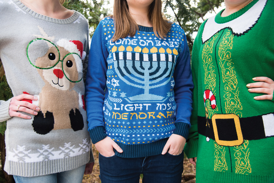 Three Northwestern students show off their holiday sweaters. GlobeMed at Northwestern has used the ugly sweater trend to raise money for the Adonai Center in Uganda through its annual fundraiser sale.