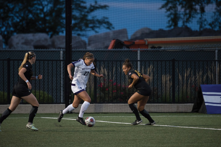 Brenna Lovera runs between two defenders. The junior forward and the Wildcats earned an at-large bid to the NCAA Tournament and will play Butler on Sunday.