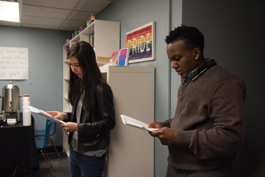 Sylvia Regan (left) and JT Turner read the names of victims of anti-transgender violence during a vigil in the Gender and Sexuality Resource Center. The event was held by Multicultural Student Affairs Monday in observance of Transgender Day of Remembrance.
