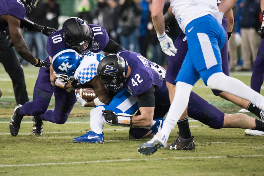 Paddy Fisher, right, makes a tackle in the Music City Bowl. The redshirt freshman linebacker is one of several NU standouts returning next season.