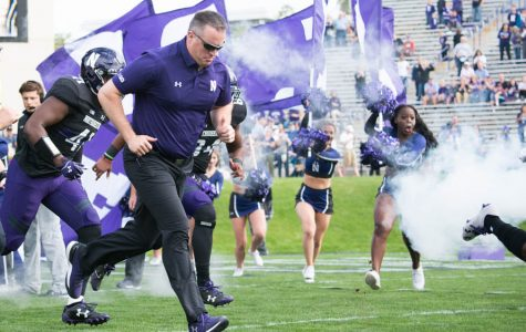 Pat Fitzgerald leads the Wildcats onto the field. Northwestern will face Kentucky in the Music City Bowl on Dec. 29.