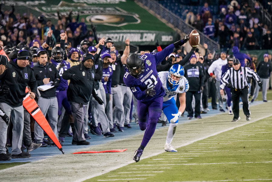 Kyle Queiro tiptoes down the sideline on an interception return. The senior safety scored a touchdown on the return to help Northwestern to a Music City Bowl victory.
