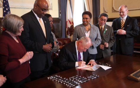 Former Gov. Pat Quinn, center, signs into law a bill ending the death penalty in Illinois in March 2011 at the State Capitol in Springfield with Kwame Raoul beside him. Quinn and Raoul are both democratic candidates for the March attorney general primary.