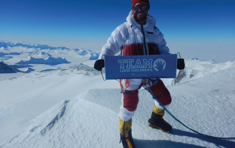 Alexander Pancoe (Weinberg '09) holds a flag for Lurie Children's Hospital at the summit of Mount Vinson in Antarctica. Pancoe raised $320,000 to donate to pediatric brain tumor research.
