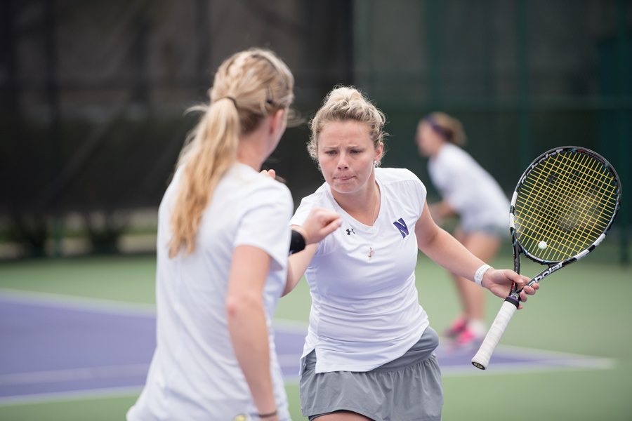 Maddie Lipp and Alex Chatt fist bump after a point. The seniors hope to lead an experienced NU squad heading into the 2018 dual match season.