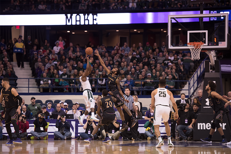 Vic Law seeks to block a Michigan State shot. The Wildcats and Spartans played a wild game Saturday.