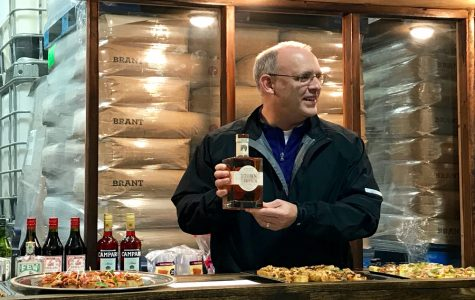 Steve Hagerty presents the Kentucky bourbon he won in a bet with Lexington Mayor Jim Gray. The event was hosted at FEW Spirits, an Evanston distillery.