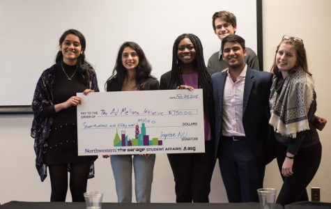 Weinberg sophomore Neha Basti receives a check after winning the Improve NU Challenge. Basti pitched The Ad Meliora Initiative to create mental health resilience programming.