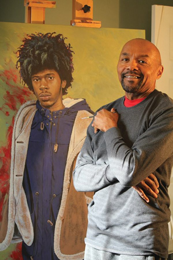 """Rick Lewis with one of the portraits from """"(In)Visible Men."""" The portrait series seeks to challenge stereotypes about black men."""